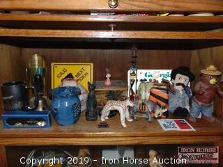 CONTENTS OF SHELF INCLUDING SMOKEY BEAR FIGURINE, ORVILLE WRIGHT, COWBELL, GLASS THERMOMETER, BERLIN SPOON